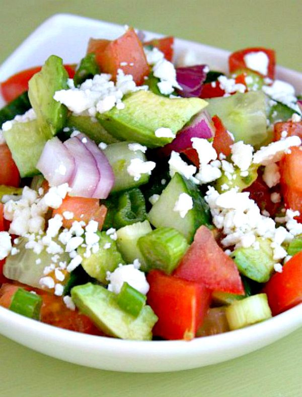 avocado cucumber tomato salad in a white bowl with a light green background