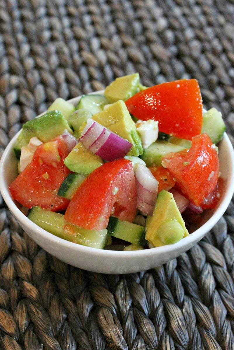 serving of avocado cucumber tomato salad in a white bowl placed on a dark brown woven placemat