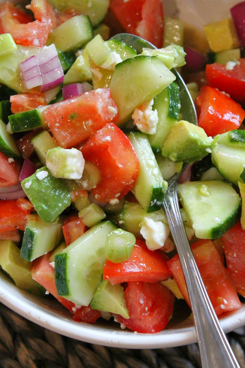 close up shot of avocado cucumber tomato salad in a white bowl with a serving spoon in it