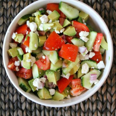 Overhead shot of avocado cucumber tomato salad in a white bowl placed on a dark brown woven place mat