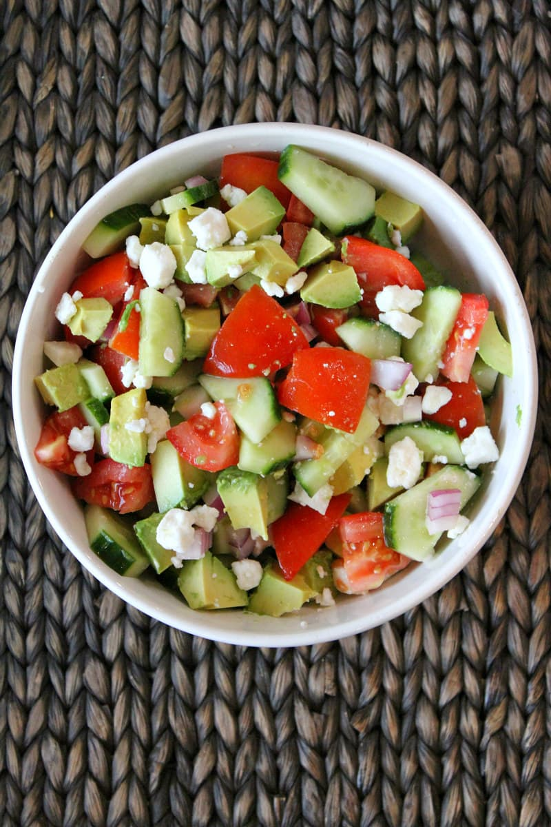 Overhead shot of avocado cucumber tomato salad in a white bowl