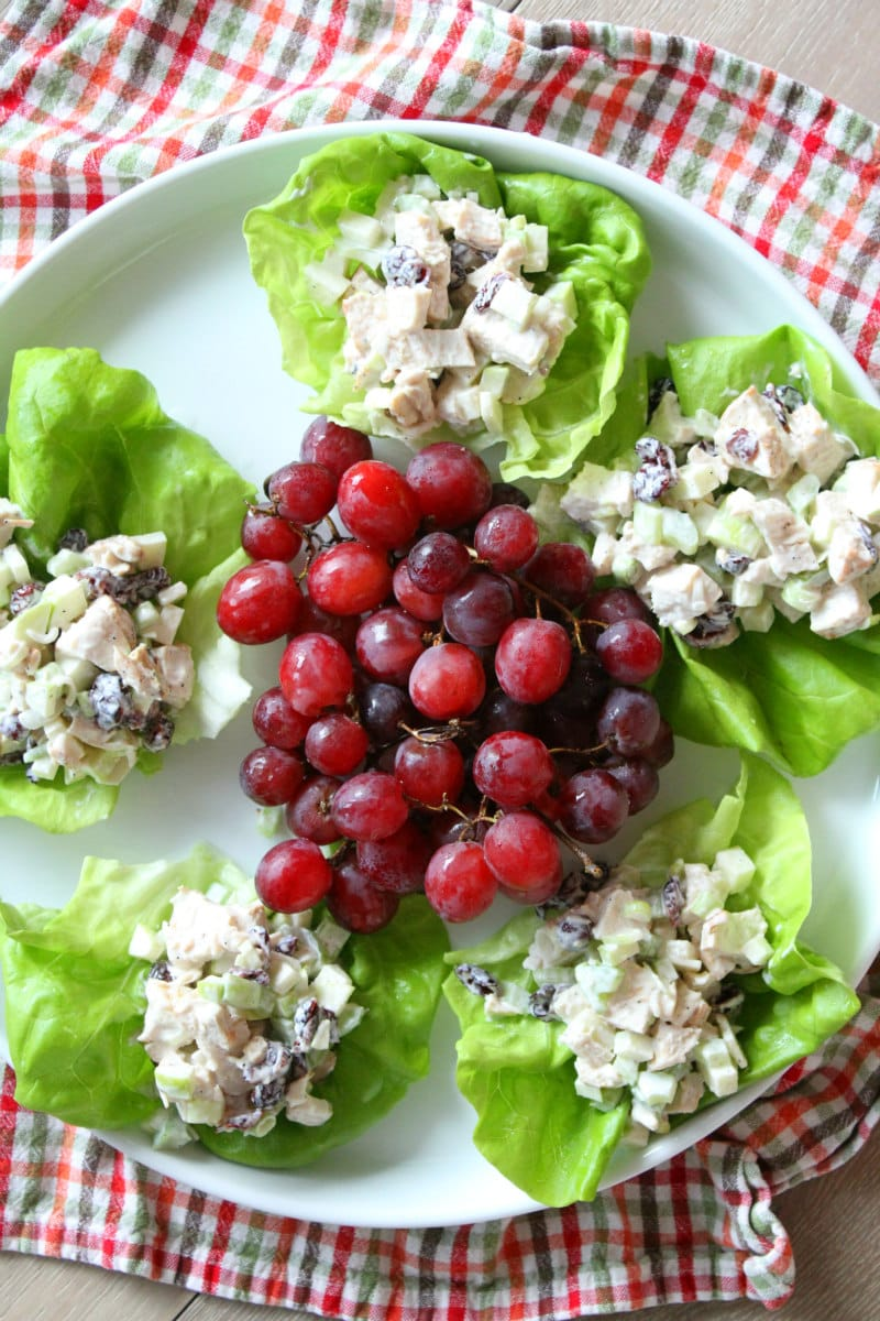 Chicken Apple Crunch Salad served in Lettuce Wraps on white plate with red grapes