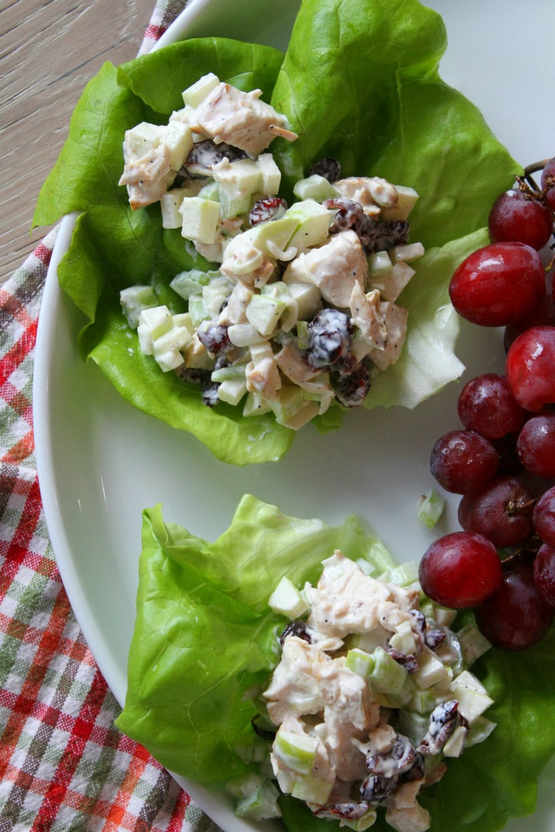 Chicken Apple Salad served in Lettuce Wraps on white plate with red grapes