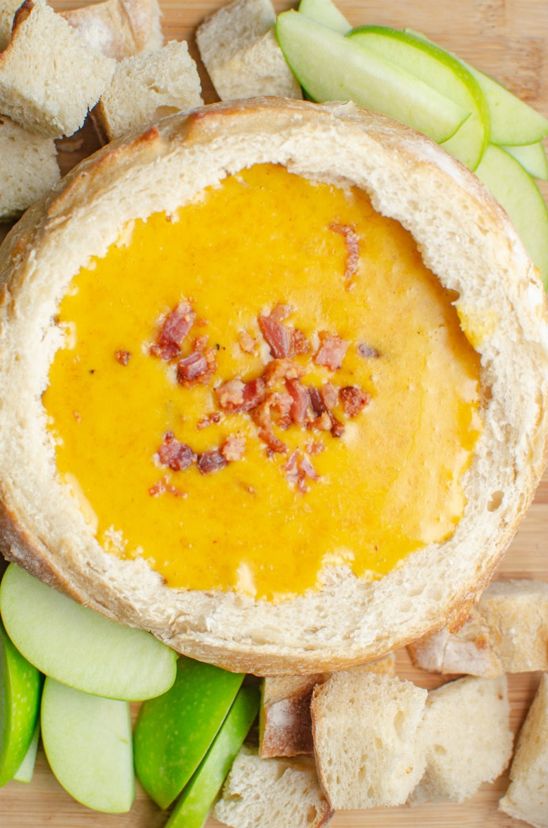 Cheddar Beer Fondue in a bread bowl with apples and bread chunks surrounding