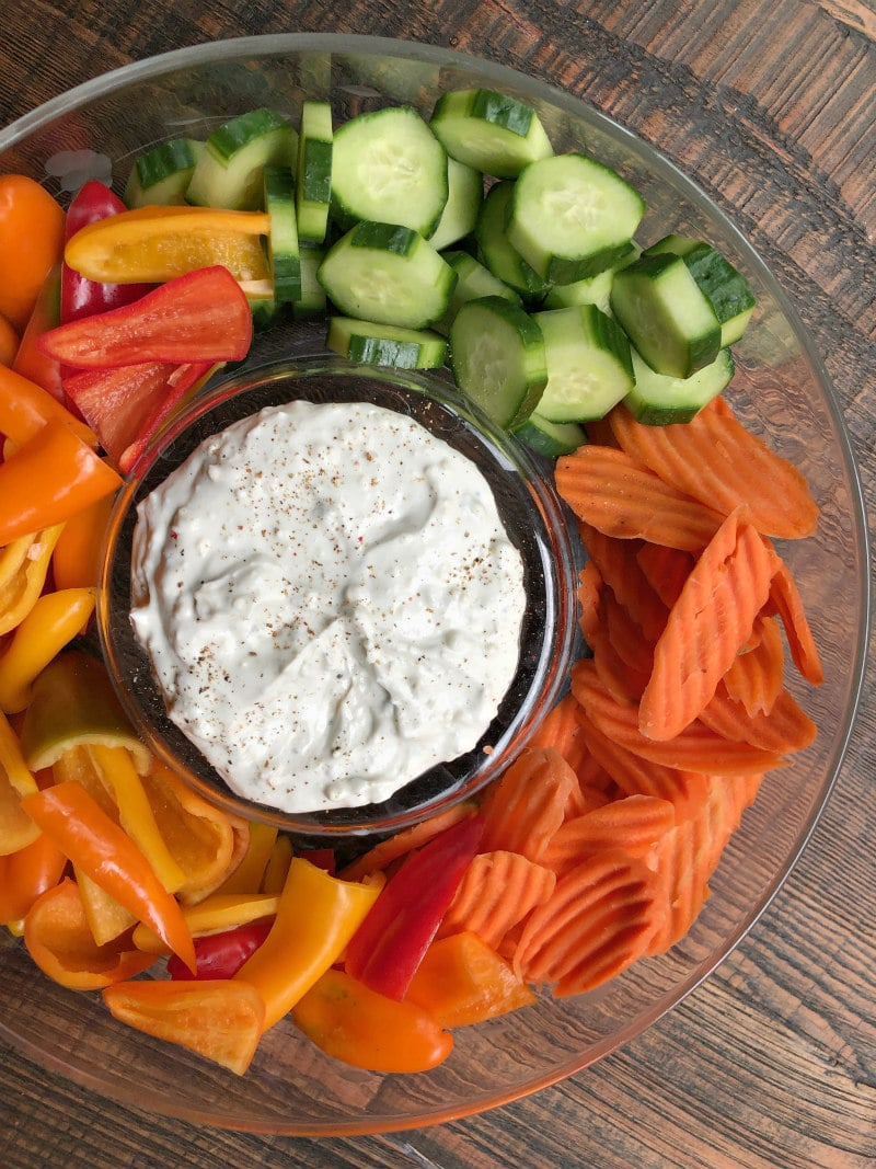 overhead shot of blue cheese dip surrounded by cucumbers, carrots and bell peppers