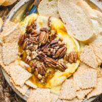 melted brie cheese with pecans on a platter surrounded by sliced baguette and crackers