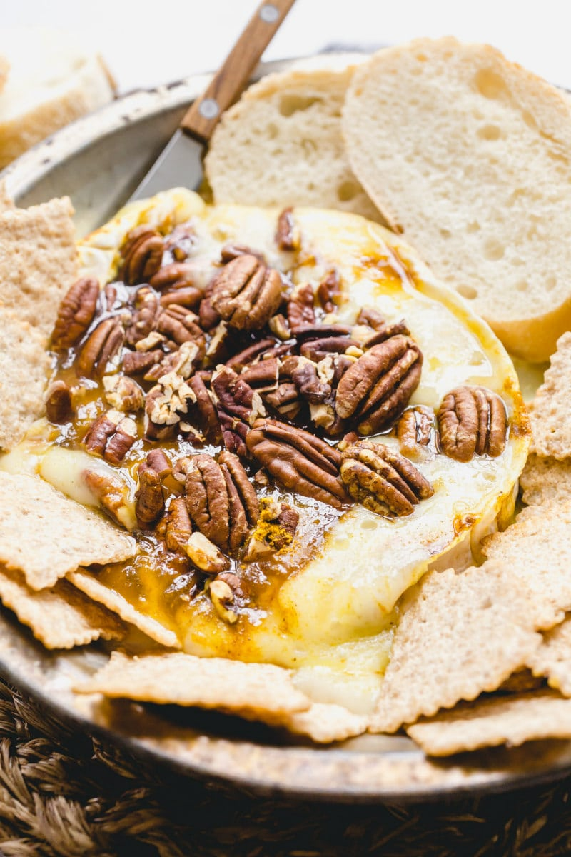 melted brie cheese with pecans surrounded by sliced baguette and crackers