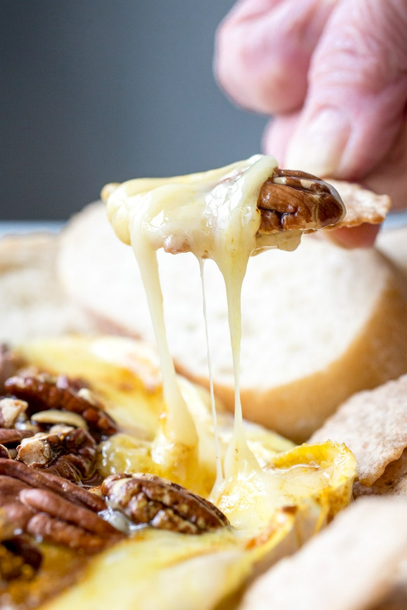 hand dipping baguette in melted brie cheese and pecans