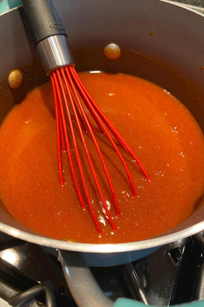 making enchilada sauce in pan stirring with red whisk