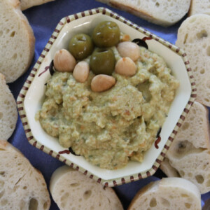 overhead shot of dish of green olive spread surrounded by baguette slices