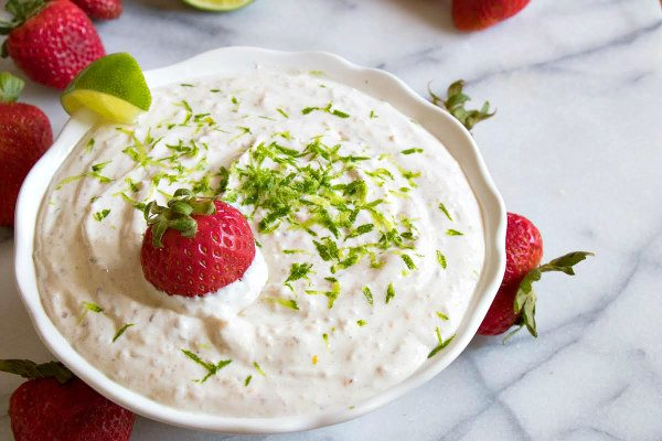 margarita fruit dip in a white bowl on a marble surface, garnished with strawberries and lime zest