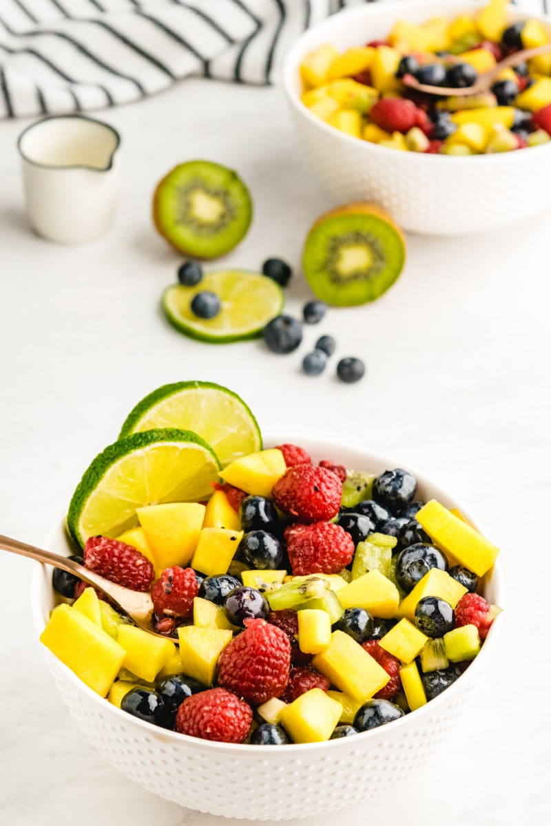 bowl of fruit salsa with spoon and lime garnish