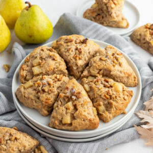 maple nut and pear scones on a white plate with fresh green pears in background