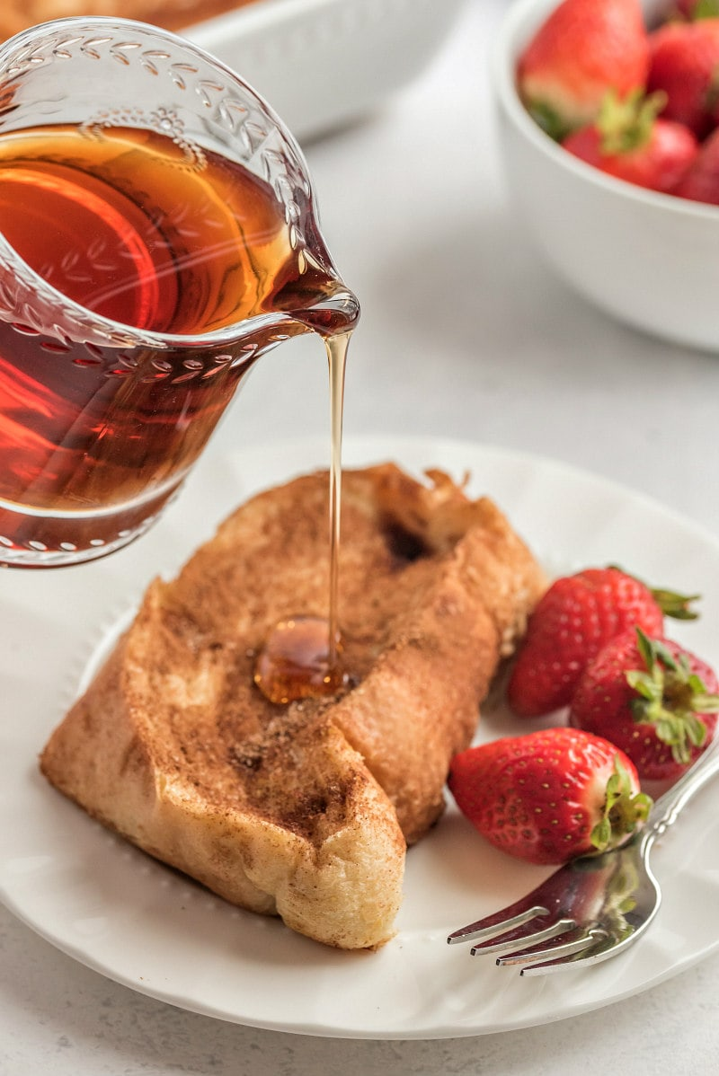 pouring syrup onto french custard toast with strawberries