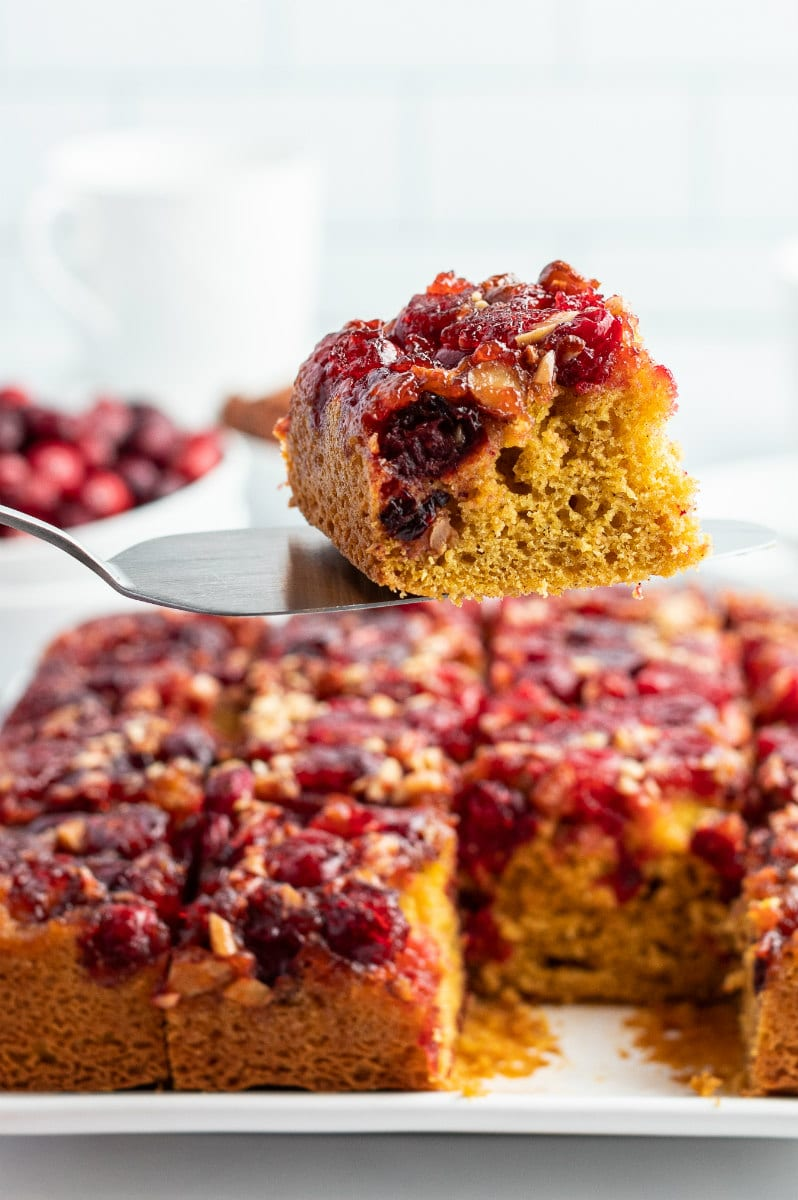 spatula showing slice of cranberry upside down cake above rest of cake