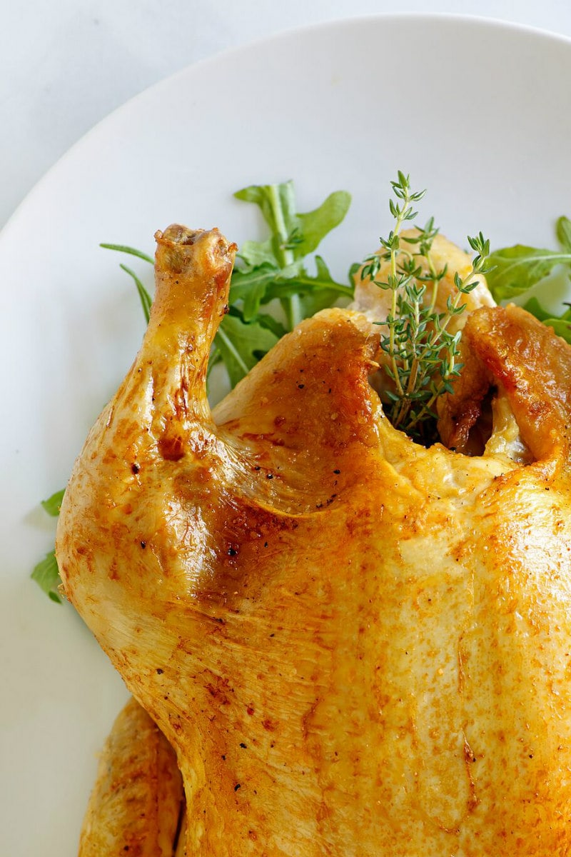 peek at corner of Cider Roasted Chicken on white platter