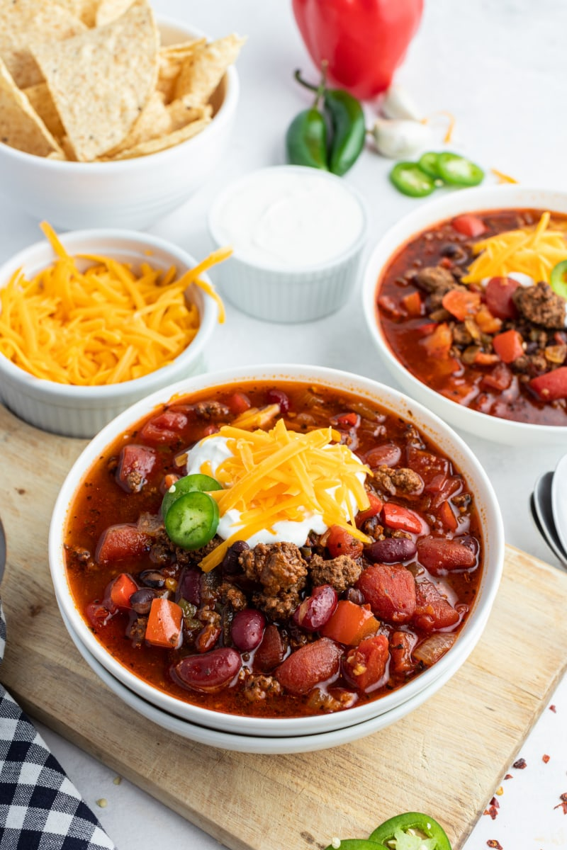 beef and bean chili in a white bowl topped with cheese and sour cream and jalapeno