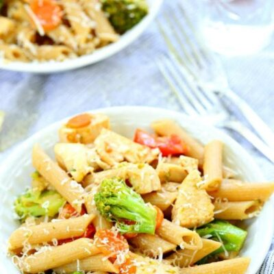 bowl of chicken pasta primavera in a white bowl with a fork on the side and another bowl of pasta in the background