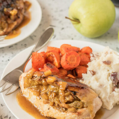 chicken breasts with curried apple stuffing on a plate with potatoes and carrots
