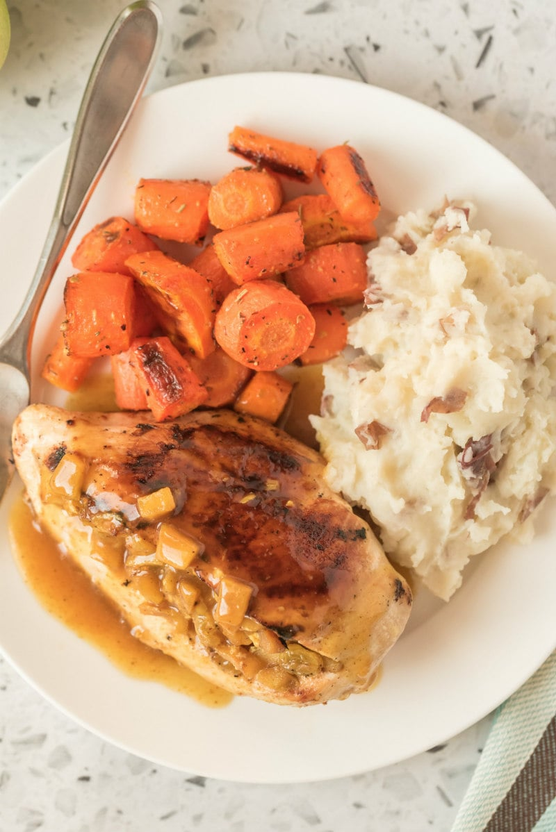 chicken with curried apple stuffing on a white plate with carrot and potato