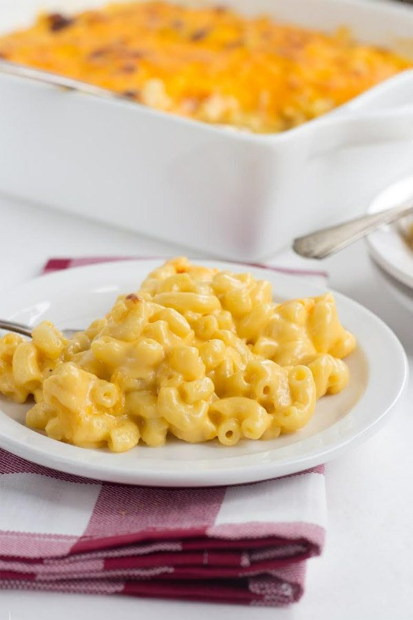 macaroni and cheese on a white plate with a red/white plaid napkin underneath and a white casserole dish in the background