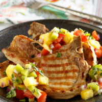 Grilled Pork Chops with tropical salsa on top set on a black dinner plate and a flowered napkin in the background