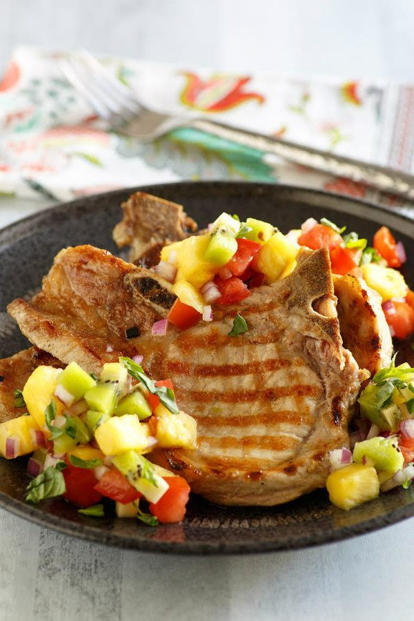 Grilled Pork Chops with Tropical Salsa set on a black plate with a fork on a flowered napkin in the background