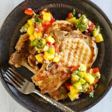 overhead shot of grilled pork chops with tropical salsa on a black plate with a fork