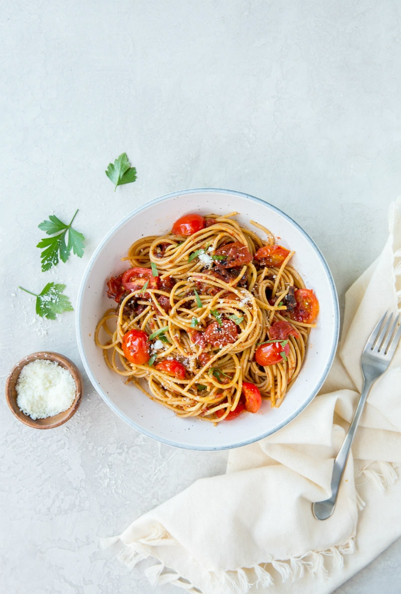 spaghetti with three tomato sauce in a white bowl with a napkin and fork on the side. bowl of salt and fresh parsley in view too