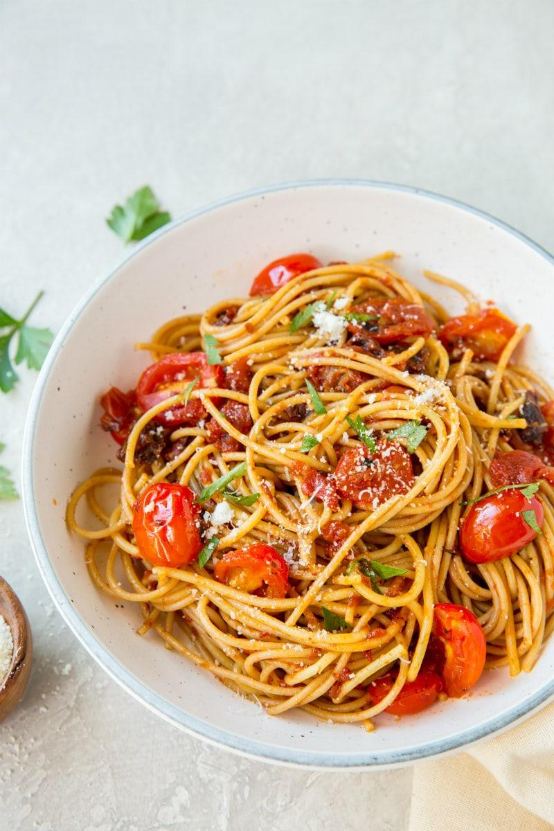 spaghetti with three tomato sauce in a white bowl