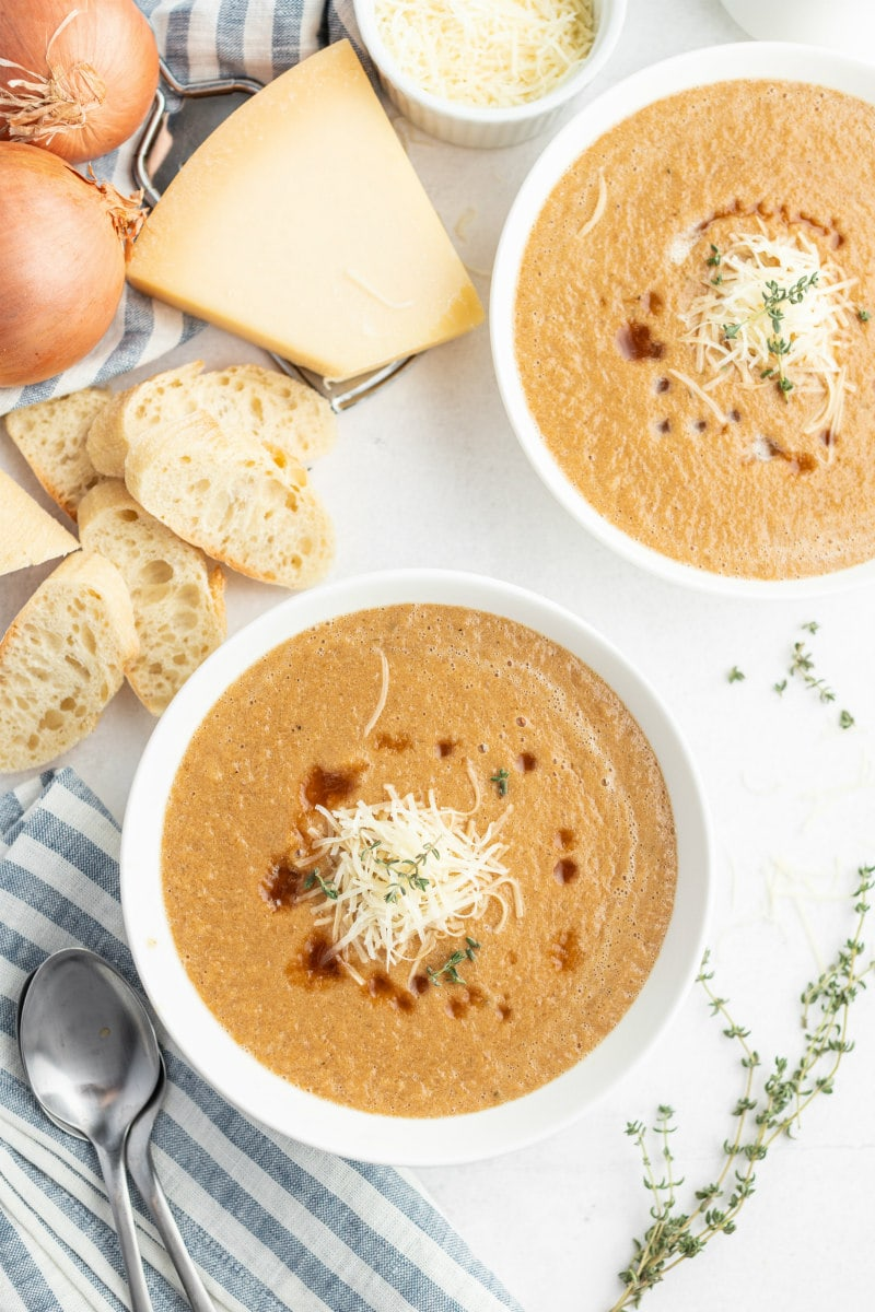 caramelized onion soup in white bowls with bread on side