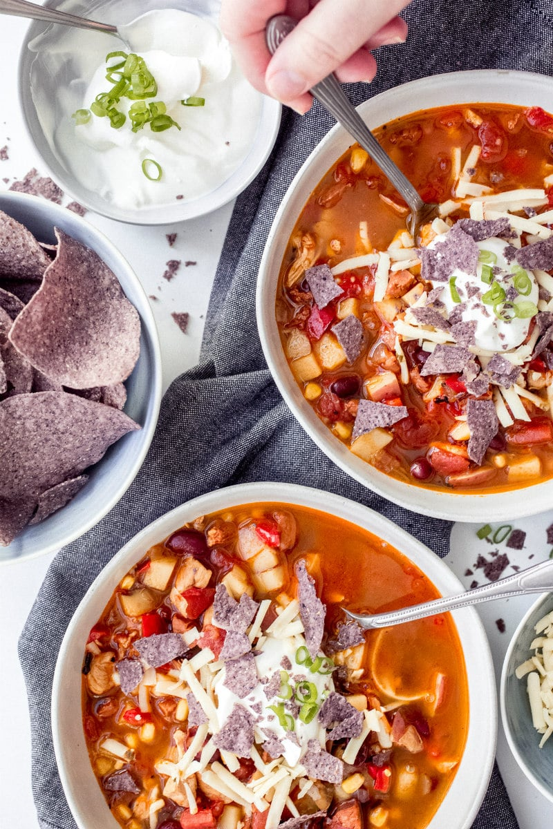 bowls of chicken tortilla sausage soup with garnishes