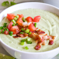 chilled avocado soup in a white bowl topped with green onion and tomato. lime wedges, cilantro and another bowl of soup in the background