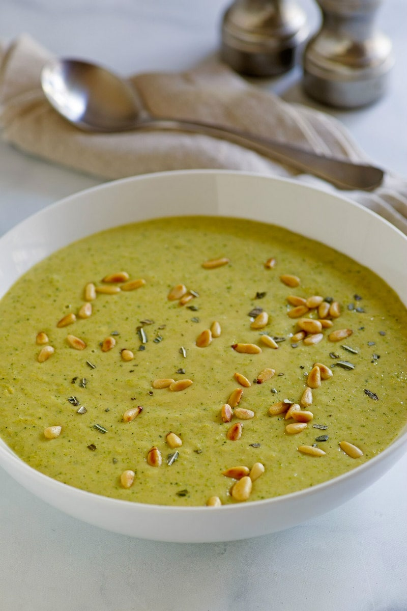 Bowl of Creamy Broccoli Soup garnished with toasted pine nuts
