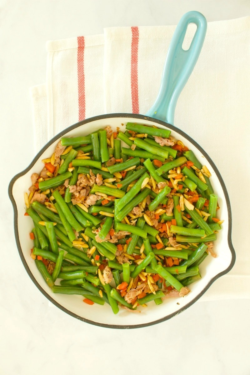 overhead shot of green beans with prosciutto in a fry pan with a blue handle, set on a yellow napkin with red stripes