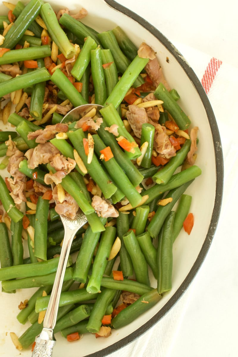 overhead shot of green beans with prosciutto in a fry pan with a serving spoon, set on a yellow napkin with red stripes