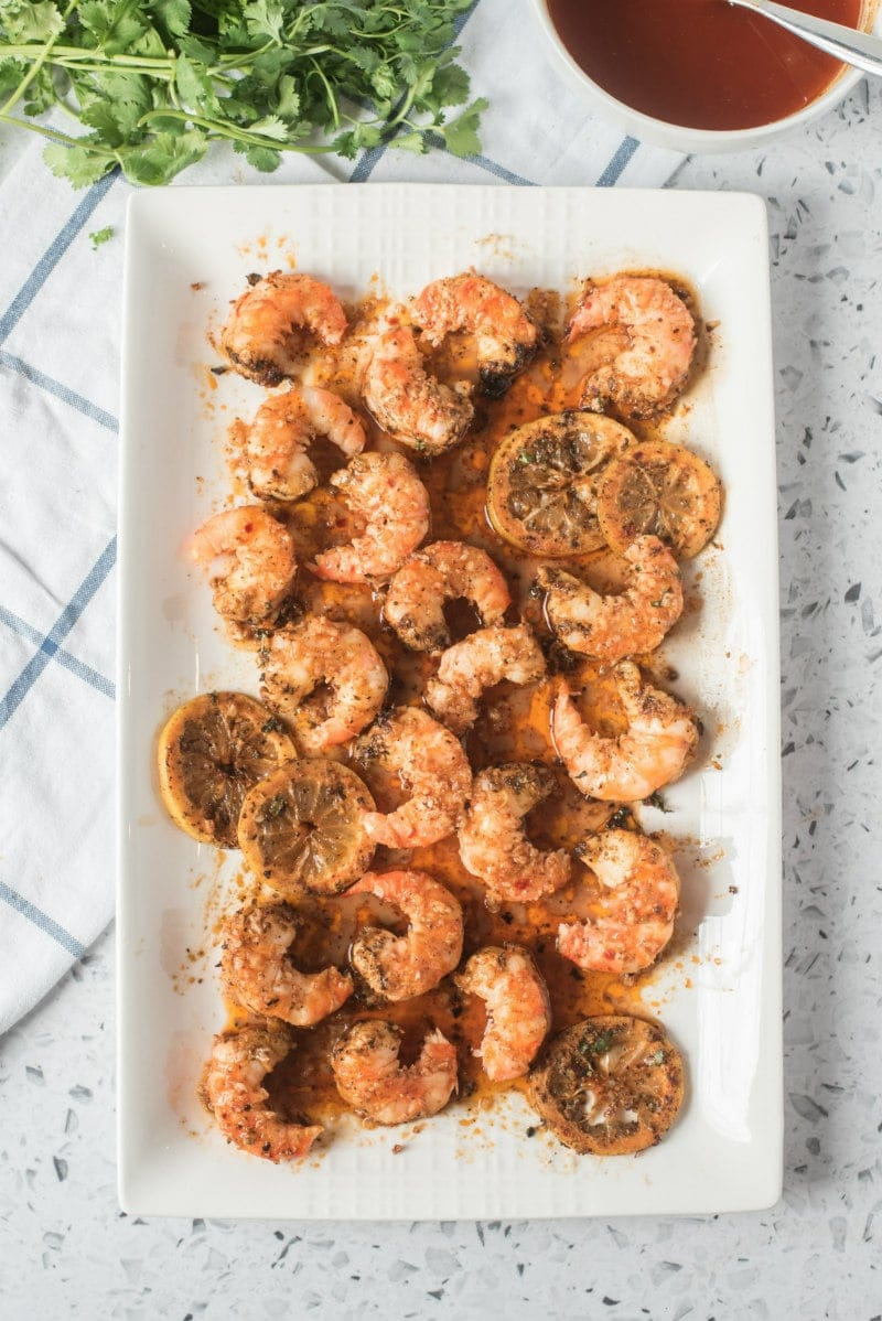 grilled jumbo shrimp on a white platter with white and blue plaid napkin underneath. peek of fresh cilantro and lemon cilantro butter on the side