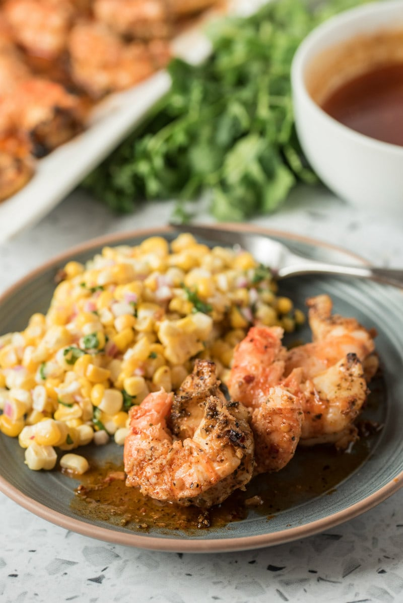 dinner plate with grilled jumbo shrimp and corn salad on it. lemon chipotle butter in a bowl displayed on the side with fresh cilantro and a tray of more shrimp in the background