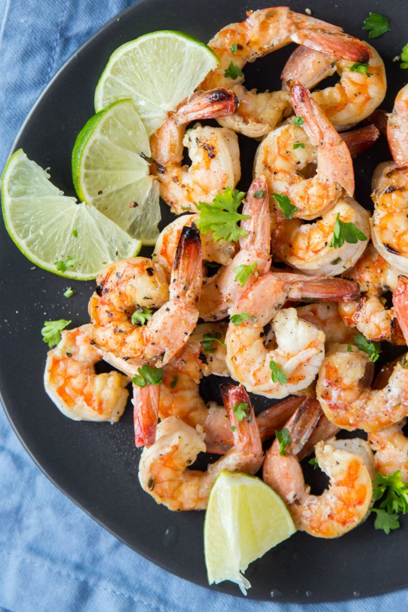 Marinated Grilled Shrimp on a black plate with lime garnish and a blue napkin underneath