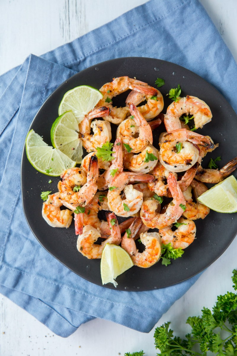Marinated Grilled Shrimp on a black plate set on a blue napkin with lime and cilantro garnish