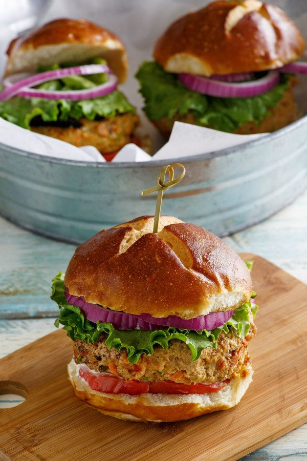 Turkey Garden Burger dressed with red onion, lettuce and tomato on a bun sitting on a wooden cutting board. galvanized metal tub in the background with two more burgers inside