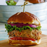 turkey garden burger dressed with lettuce and tomato in a bun with a sandwich pick on top, sitting on a wooden cutting board. galvanized metal tub in background