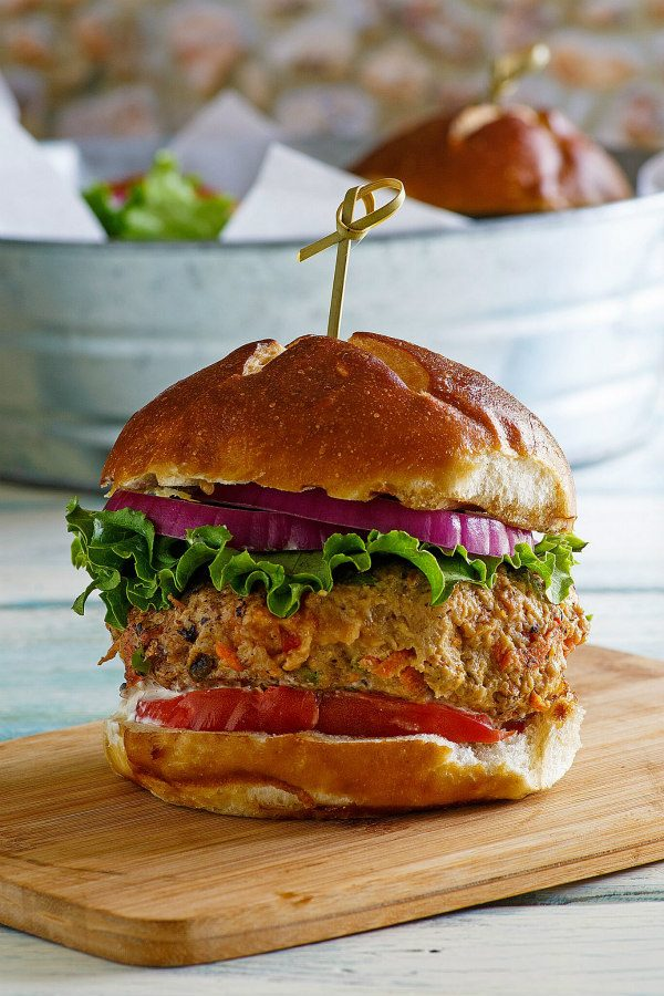 Turkey Garden Burger dressed with red onion, lettuce and tomato on a bun sitting on a wooden cutting board. galvanized metal tub in the background