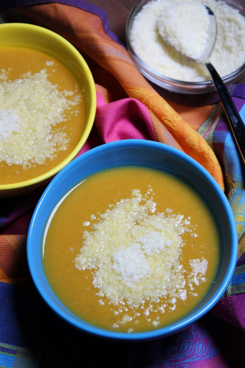 Bowls of Tuscan Pumpkin White Bean Soup served with grated Parmesan cheese