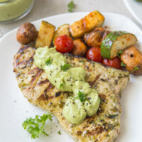 grilled swordfish topped with avocado mayonnaise on a white plate. Vegetables on the side.