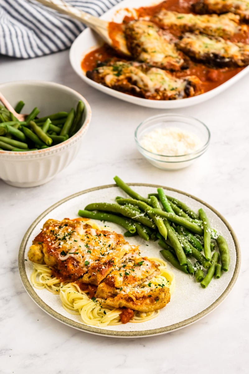 veal parmesan on a plate with green beans