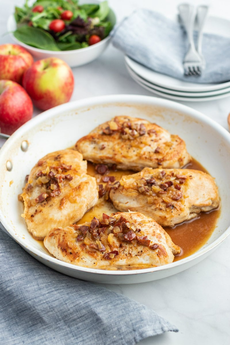 chicken with cider and bacon sauce in white skillet