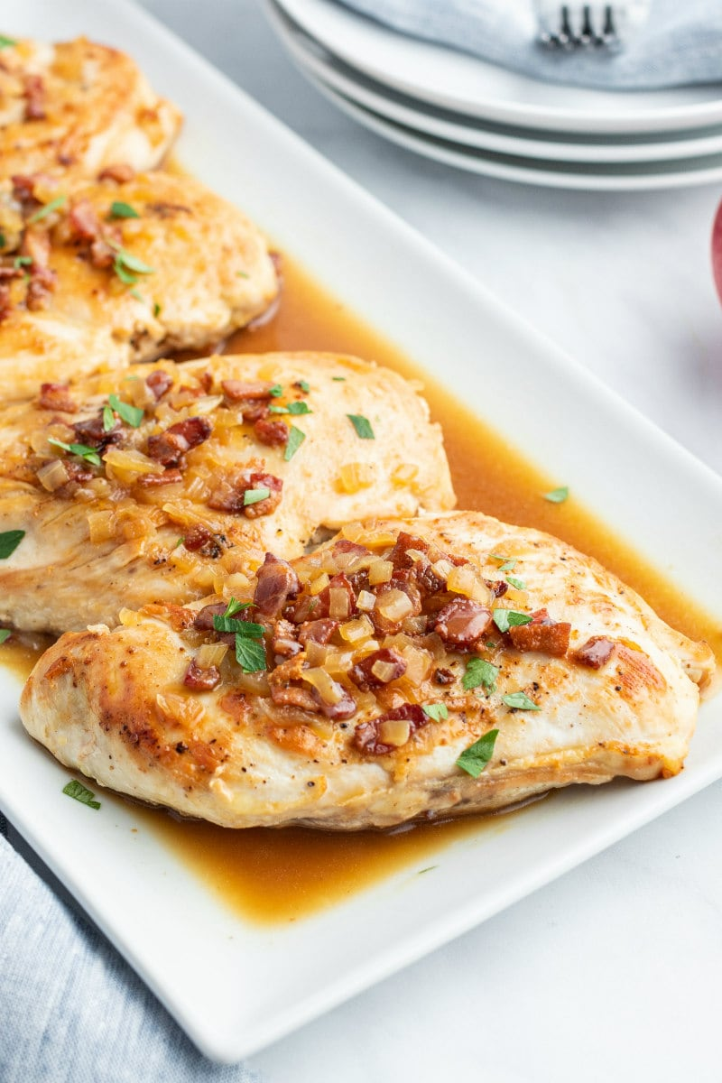 chicken with cider and bacon sauce on white platter