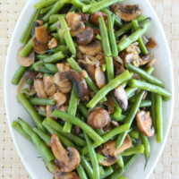 overhead shot of green beans with mushrooms and shallots on a white platter set on a woven white placemat