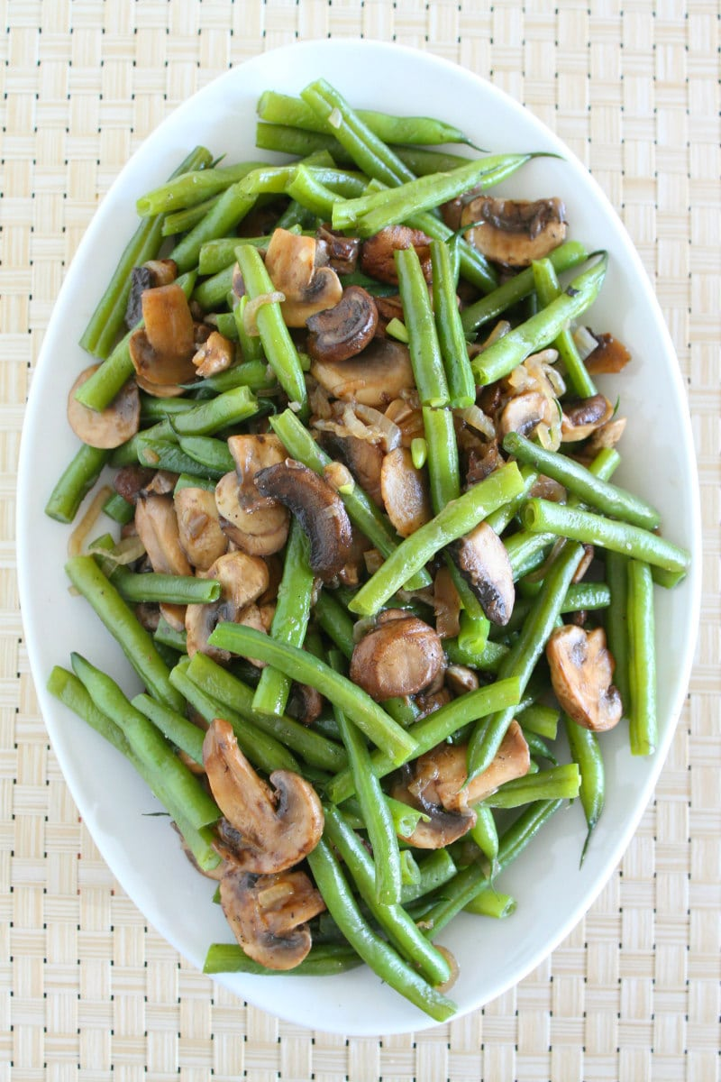 overhead shot of Green Beans with Mushrooms and Shallots on a white serving platter set on a woven white placemat